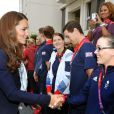Kate Middleton, qui salue ici la cycliste Victoria Pendleton, le prince William et le prince Harry en visite au QG du Team GB, dont ils sont ambassadeurs, au village olympique de Stratford, à Londres, le 31 juillet 2012.