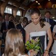 La princesse Victoria de Suède se voit offrir un bouquet de fleurs par une petite fille lorsqu'elle assiste à une commemoration pour le centenaire de la naissance de Raoul Wallenberg à Sigtuna le 4 août 2012
