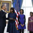 Barack Obama prête serment devant le juge de la Cour suprême John Roberts, accompagné par sa femme Michelle Obama, dans le Salon Bleu de la Maison-Blanche, à Washington, le 20 janvier 2013.
