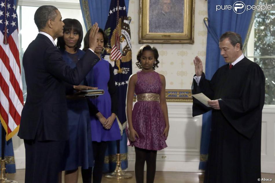 Barack Obama prête serment devant le juge de la Cour suprême John Roberts, accompagné par sa femme Michelle Obama et ses filles Malia et Sasha, dans le Salon Bleu de la Maison-Blanche, à Washington, le 20 janvier 2013.