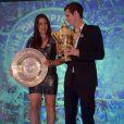 Marion Bartoli pose avec le trophée de Wimbledon lors du dîner des champions au côté d'Andy Murray à l'hôtel Intercontinental de Londres le 7 juillet 2013