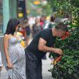 Alec Baldwin et sa femme Hilaria Thomas (enceinte) sont allés prendre leur petit-déjeuner dehors. Sur le chemin de retour vers leur domicile, Alec Baldwin s'est arrêté pour sentir le parfum de fleurs sur le trottoir. New York, le 19 août 2013.