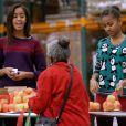 Barack Obama a distribué des colis de nourriture avec ses jolies filles Malia et Sasha, ainsi que son épouse Michelle, dans les locaux de l'association Capital Area Food Bank à Washington, le 27 novembre 2013.
