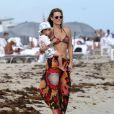 Molly Sims, superbe en bikini, avec son fils Brooks sur la plage à Miami, le 23 décembre 2013.