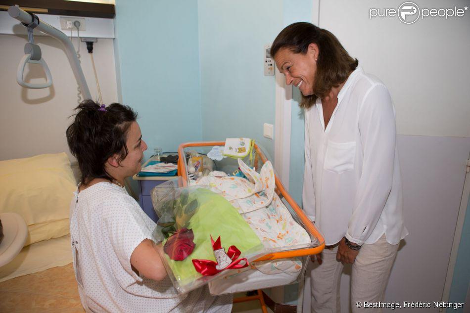La princesse Stéphanie de Monaco, rose et layette à la main, a rencontré de jeunes mamans et leurs bébés au Centre hospitalier Princesse Grace, le 27 mai 2014, dans le cadre de la Fête des mères.