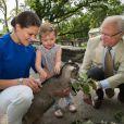 La princesse héritière Victoria, la princesse Estelle, fascinée par une biquette, et le roi Carl XVI Gustaf de Suède sont allés ensemble à Skansen, le musée en plein air et zoo de Stockholm, le 11 juillet 2014. Trois générations de souverains réunis dans la bonne humeur.