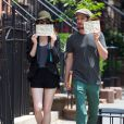 Emma Stone et son petit-ami Andrew Garfield se cachent le visage avec chacun un message en sortant d'un déjeuner au Cafe Cluny à New York, le 17 juin 2014. Sur leurs papiers on peut lire qu'ils n'ont pas besoin de publicité mais que les associations mentionnées en ont vraiment besoin.