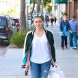 Hilary Duff quitte le magasin Intermix à Beverly Hills, habillée d'une veste  varsity  à roses brodées Closed, d'un t-shirt blanc, d'un jean déchiré aux genoux et de baskets Saint Laurent. Le 24 mars 2015.