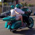 Exclusif - Miley Cyrus monte derrière un inconnu sur sa moto Harley Davidson pour profiter d'une escapade colorée avec un casque assorti avant de continuer la route avec ses amis dans leur Porsche décapotable à Hollywood, le 12 avril 2015.