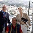 Le prince Albert II de Monaco, son épouse la princesse Charlene accompagnée de son petit chien Monte, lors de leur visite aux spectateurs de la tribune de l'association monégasque des handicapés moteur, lors des essais du Grand Prix de Monaco le 23 mai 2015