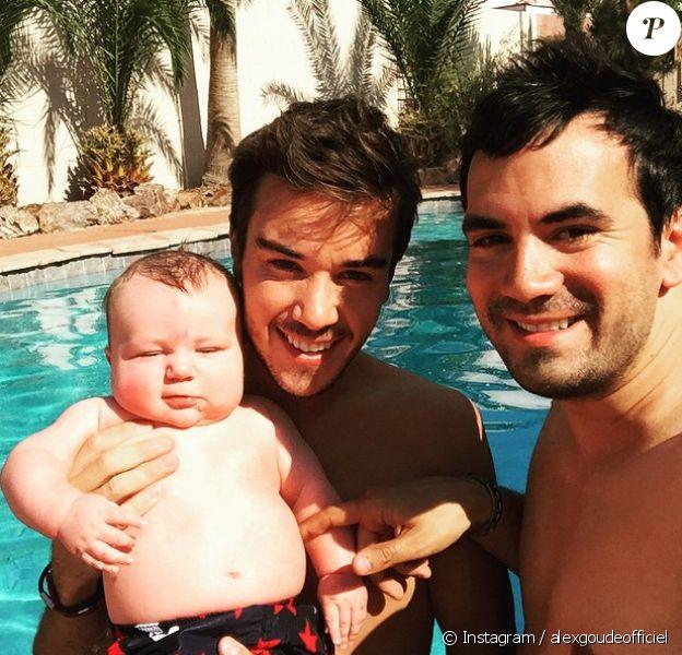 Alex Goude, Romain et leur bébé Elliot posent ensemble dans la piscine. Juin 2015.