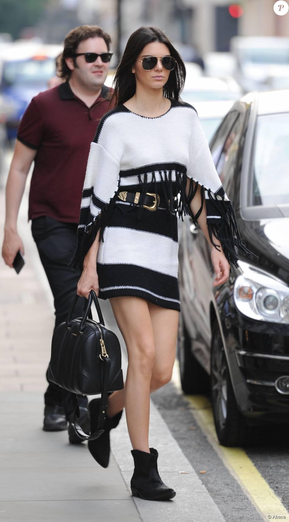 Kendall Jenner en robe noire et blanche style poncho à franges Givenchy, accessoirisée d'un sac Givenchy et d'une ceinture B-Low, à Londres le 1 er  juillet 2015