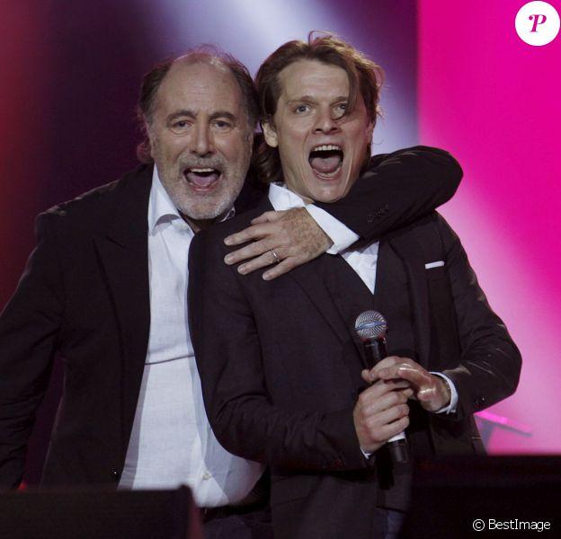 """Michel Delpech et le chanteur Bénabar sur scène, lors du concert """"Touche pas à mon pote"""", organisé par l'association SOS Racisme au Champ de Mars, à Paris, le 14 juillet 2011."""