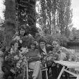 Archives - Anne-Marie Peysson, assise au centre entourée de ses amis avec des fleurs, dont Michel Delpech (en haut à gauche), Gérard Bourgeois et Jacqueline Huet à Croissy-sur-Seine, le 1er mai 1968 dans le jardin de la maison d'Anne-Marie Peysson, qui prépare la sortie de son deuxième album.