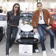 """Exclusif - Anthony Delon pose avec Corentine, la femme de Samuel Lecomte qui pilotera la Jaguar Type E de 1962, lors de la 26ème édition du Tour Auto au Grand Palais à Paris, le 24 avril 2017. Il est venu à cet événement où 2 voitures, une Jaguar type E 1962 et une Alpine Renault de 1964 portent les couleurs de sa nouvelle collection de vêtements en cuir """"Anthony Delon 1985"""". © Pierre Perusseau/Bestimage"""