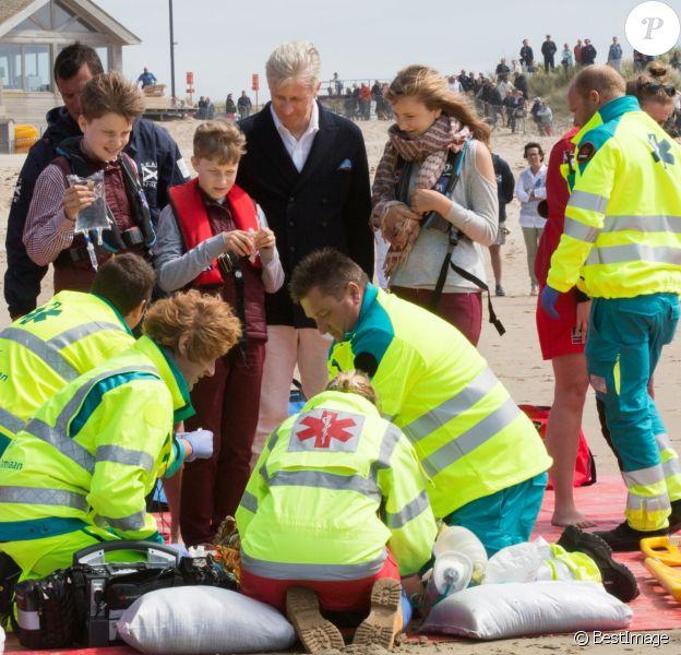 Le roi Philippe et la reine Mathilde de Belgique ainsi que leurs quatre enfants la Princesse Elisabeth, le Prince Gabriel, le Prince Emmanuel et la Princesse Eléonore ont assisté et même participé à des exercices de sauvetage, comme ici des manoeuvres de réanimation, sur la plage de Middelkerke, le 1er juillet 2017.