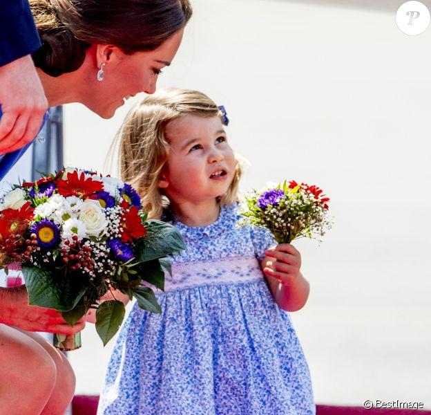 La princesse Charlotte avec son mini-bouquet de fleurs offert par le gouvernement allemand. Arrivée du prince William et de Kate Middleton avec leurs enfants George et Charlotte de Cambridge à l'aéroport de Berlin-Tegel en Allemagne le 19 juillet 2017 lors de leur visite officielle.