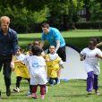 Le prince Harry joue avec des enfants lors de sa visite du centre de loisirs Newham Council's à Central Park à Londres, le 28 juillet 2017.