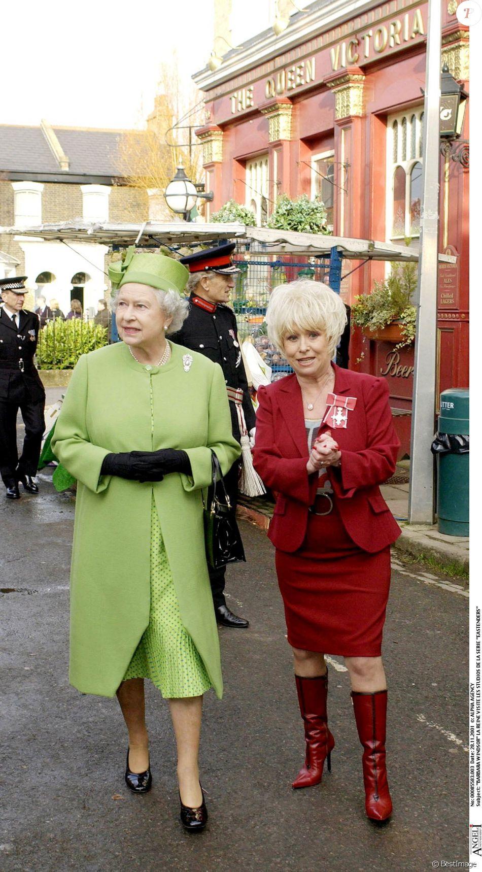 Barbara Windsor En Tailleur Rouge Recevant La Visite De Reine Elizabeth II Et