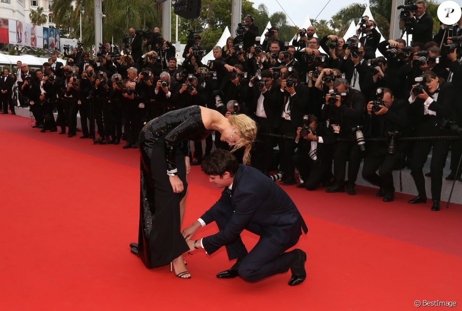 """Niels Schneider rattachant la chaussure de Virginie Efira - Montée des marches du film """"Sibyl"""" lors du 72ème Festival International du Film de Cannes. Le 24 mai 2019 © Jacovides-Moreau / Bestimage"""