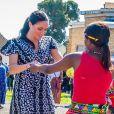 Meghan Markle, en robe Mayamiko, et le prince Harry, duc de Sussex, en visite dans le township de Nyanga, Afrique du Sud. Le 23 septembre 2019.