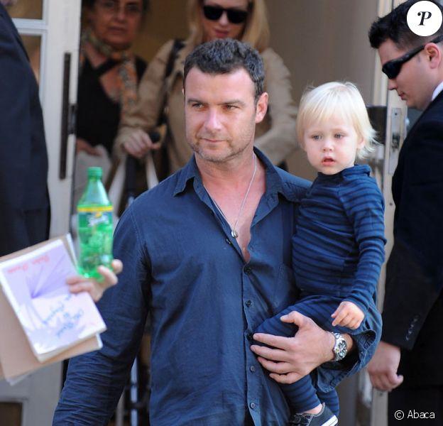 Naomi Watts (en arrière-plan) et Liev Schreiber portant leur fils aîné Alexander sortant de leur appartement à New York le 10 juillet 2009