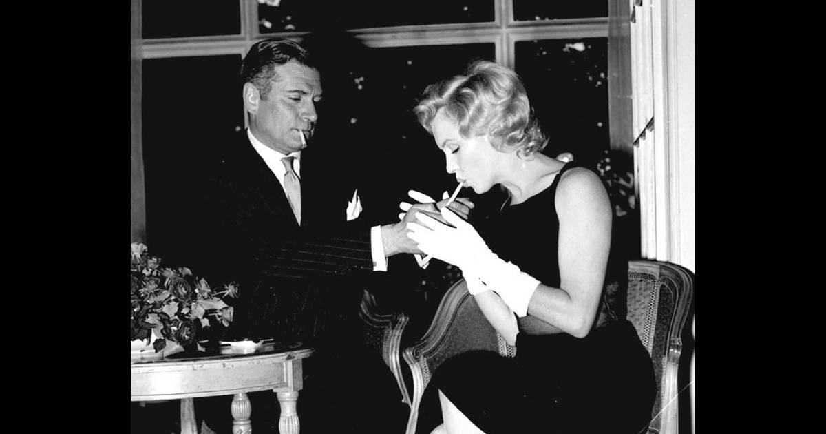 laurence olivier allume la cigarette de l 39 actrice marilyn monroe avec qui il joue et qu 39 il. Black Bedroom Furniture Sets. Home Design Ideas