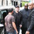 John Travolta, entouré de gardes du corps, s'apprête à entrer dans le restaurant asiatique Dave à Paris le 20 juin 2011