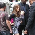 Kelly Preston porte son petit Benjamin alors qu'elle s'apprête à entrer dans le restaurant Dave à Paris le 20 juin 2011