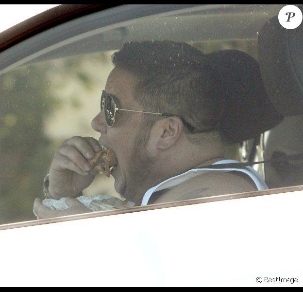 Dans sa BMW, dont le pare-choc arrière est endommagé depuis presque un mois, Chaz Bono finit de déjeuner avant de rentrer chez lui dans sa demeure de West Hollywood le 22 août