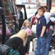 Mère au petit soin, Claudia Schiffer refait le lacet de son fils Caspar (8 ans). Londres, le 18 octobre 2011.