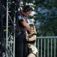 La chanteuse Fergie, déchaînée et se frottant contre un technicien lors du show des Black Eyed Peas à Londres. Le 1er juillet 2011.