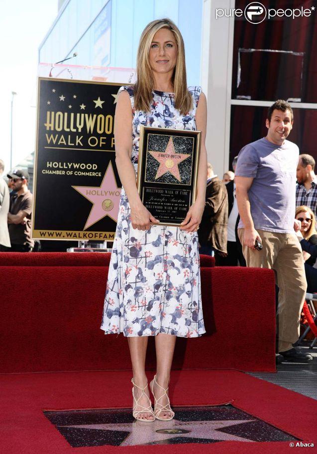Jennifer Aniston, soutenue par Adam Sandler, reçoit son étoile sur le Walf of Fame, à Los Angeles, le 22 février 2012.