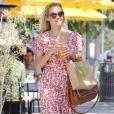 Reese Witherspoon est une fan des petites robes fleuries, qu'elle accessoirise ici avec un sac Chloé et des compensées : un look parfait pour la saison.