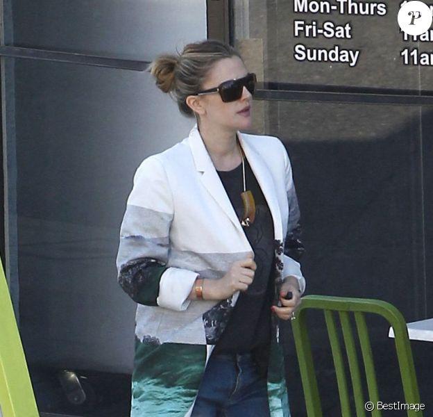 Drew Barrymore, enceinte, tente de cacher son ventre sous un improbable manteau, en compagnie de son fiancé Will Kopelman, le 20 avril 2012 à Beverly Hills