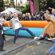 """""""Zinedine Zidane et Sophie Thalmann s'essaient au babyfoot géant le 7 juin 2012 lors d'une journée de mobilisation organisée par ELA dans les rues de Paris près du Parc Monceau"""""""