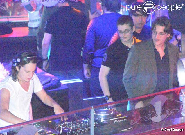 Pierre Sarkozy, alias DJ Mosey, mixe pendant que ses frères Louis et Jean l'observent lors de la soirée au Queen, boîte de nuit des Champs-Elysées à Paris, le 22 juin 2012