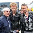 Matthew Bellamy et Dominic Howard accompagnent Bernie Ecclestone dans le paddock du Grand Prix de Formule 1 de Grande Bretagne à Silverstone le 8 juillet 2012