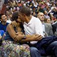 Michelle et Barack Obama, surpris par la Kiss Cam du stade, s'embrassent durant un match de basket-ball opposant l'équipe de Brésil aux États-Unis. À leurs côtés, leur fille aînée Malia et le vice président Joe Biden. À Washington, le 16 juillet 2012.