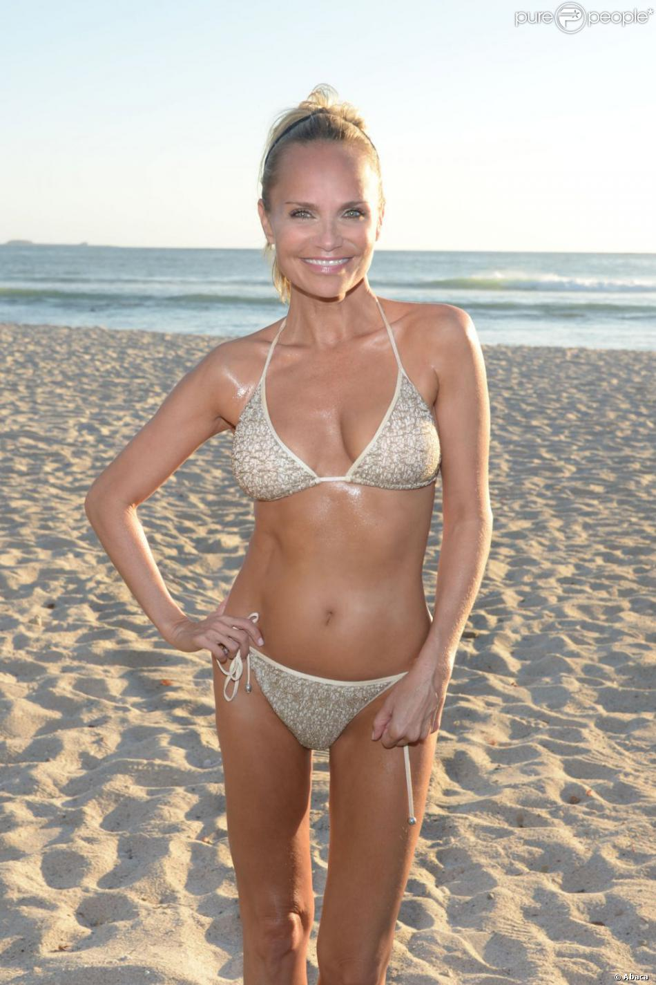 With her slim body and Light blond hairtype without bra (cup size 32B) on the beach in bikini