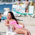 En monokini rose et rarement sans un verre à la main, Tulisa Contostavlos ne risque pas de passer inaperçue à la plage, en vacances à Ibiza le 10 juillet 2013