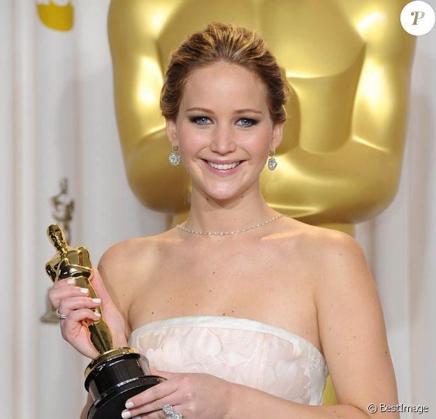 """Jennifer Lawrence (robe Dior Haute Couture) et son Oscar de la meilleure actrice pour son rôle dans """"Happiness Therapy"""" le 24 février 2013."""