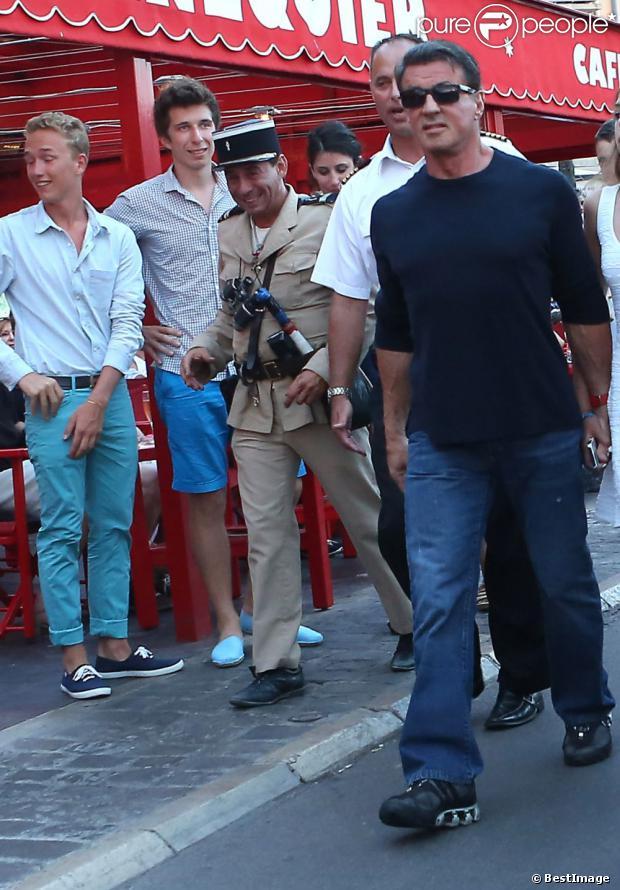 Un gendarme déguisé approche Sylvester Stallone au côté de sa femme Jennifer Flavin et ses filles Sophia, Sistine et Scarlet en vacances à Saint-Tropez le 3 août 2013.
