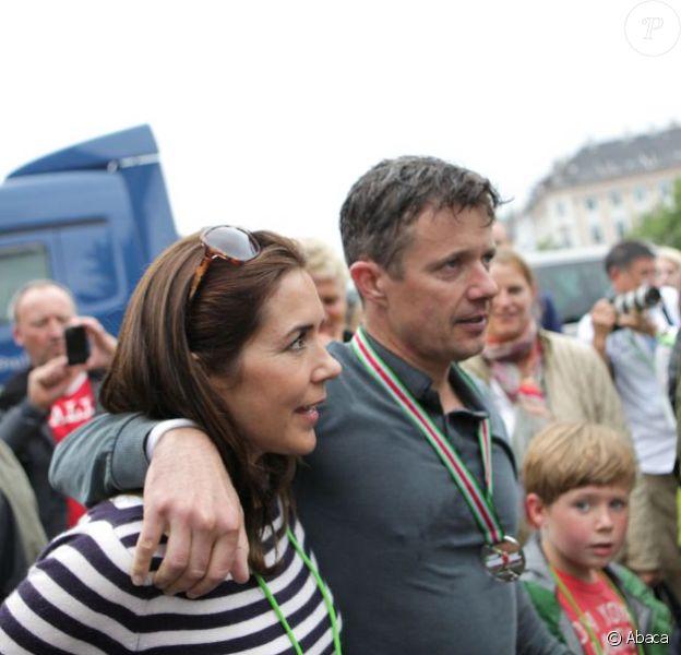 """Un peu de soutien pas de refus, après la ligne d'arrivée... Sous les yeux et les encouragements de son épouse la princesse Mary et leurs enfants Christian et Isabella, le prince Frederik de Danemark a couru dimanche 18 août 2013 l'Ironman de Copenhague : avec un chrono remarquable de 10h45'32'', il s'est classé 706e parmi les 2 600 participants. Dans le détail, Frederik de Danemark a effectué les 3,8 km de natation en 1h10'16"""", a bouclé ses 180 km à vélo en 5h25'19"""", et a rallié la ligne d'arrivée en courant son marathon en 3h58'47"""""""