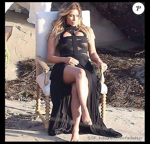 Kim Kardashian, canon dans sa robe Alexander McQueen lors d'un shooting photo sur une plage.