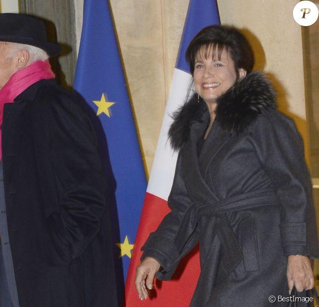 Anne Sinclair tout sourire et son compagnon Pierre Nora arrivent au Palais de l'Elysée à Paris le 9 decembre 2013. L'historien a été élevé, par François Hollande, au grade de grand officier de la Légion d'honneur.