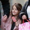 Suri Cruise, souriante, déguste un esquimau alors qu'elle se promène avec sa nounou et son garde du corps à New York, le 11 décembre 2013.