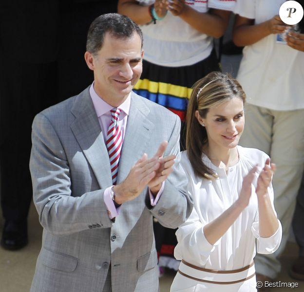"""Le roi Felipe VI et la reine Letizia d'Espagne applaudissent en choeur les jeunes participants du 29e programme culturel """"Ruta BBVA 2014"""", dédié au Pérou, au palais royal du Pardo à Madrid, le 21 juillet 2014."""