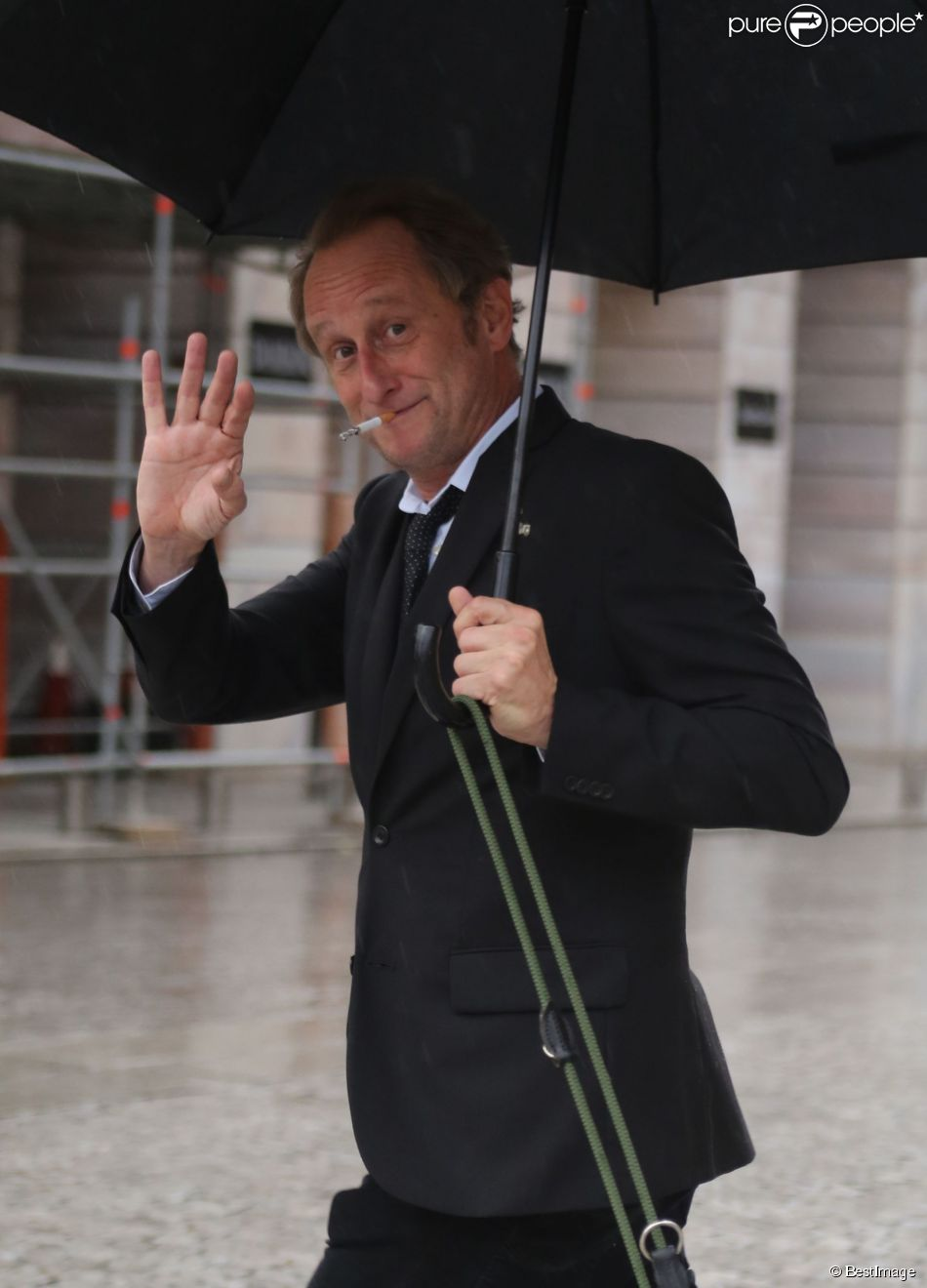 Exclusif - Benoît Poelvoorde promène son chien sous la pluie place Vendôme à Paris le 3 août 2014.