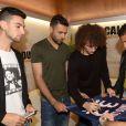 David Luiz dédicace un maillot du PSG à son nom tenu par ses coéquipiers du PSG Salvatore Sirigu et Marquinhos. Soirée de lancement de Call of Duty : Advances Warfare, le 3 novembre 2014 à Paris